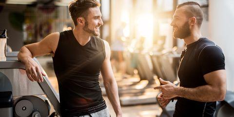 Twee mannen praten met elkaar in de sportschool en vragen of alles goed gaat.