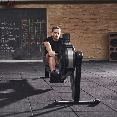 Two young sportsmen training on rowing machine