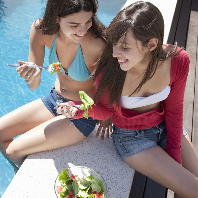 two young women eating salad by the pool