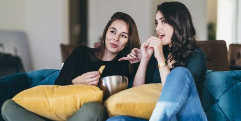 Two young women friends watching tv at home