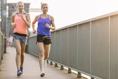 Two young women running on bridge