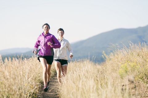 Two young women trail running in the mountains on an early morning.