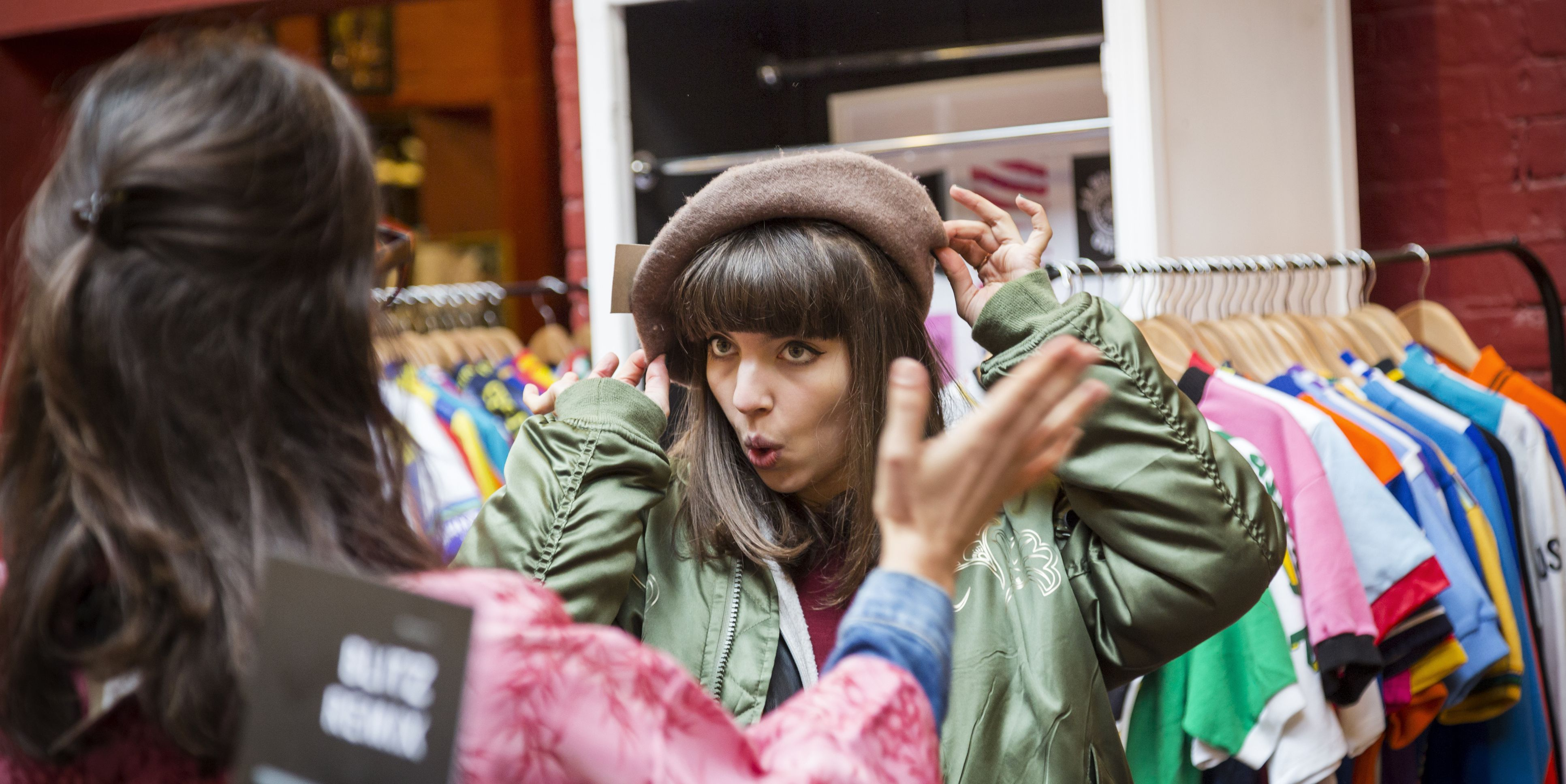 Two young women trying on beret at vintage clothes stall