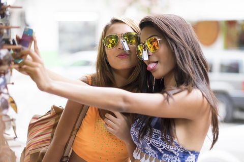 Two young women trying sunglasses on and taking a selfie