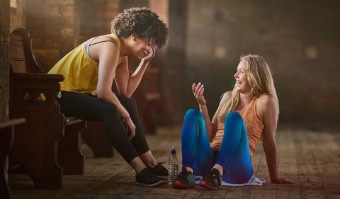 Two young women wearing sports clothing talking in gym.