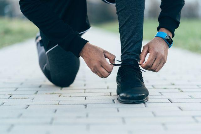 ウォーキングをする男性が靴ひもを結ぶ
