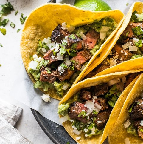 carne asada tacos with guacamole on paper and grey plate