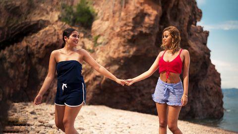 dos chicas se dan la mano en una playa