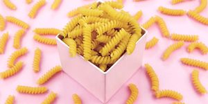 Uncooked italian pasta on pink background.