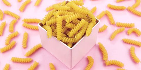 Uncooked italian pasta on pink background.