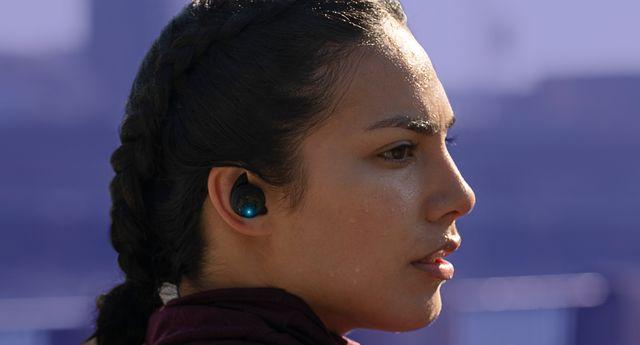 woman wearing under armour true wireless flash x earbuds by jbl