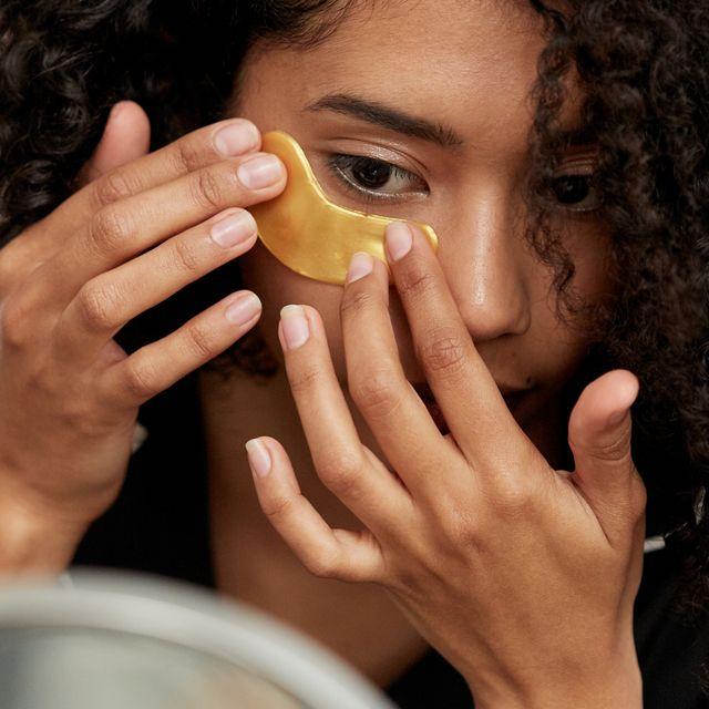 woman applying gold under eye mask