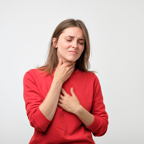 unhappy caucasian woman in red pulover suffering from throat pain at home