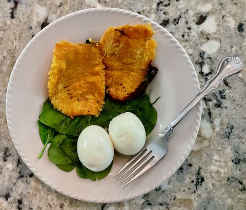 two soft boiled large organic eggs and a roasted hannah sweet potato over spinach, one of my go to lunches