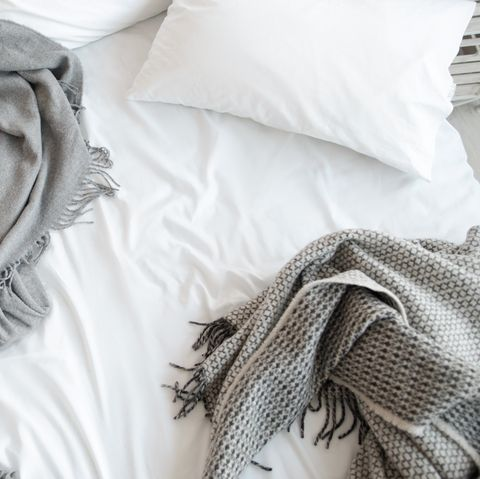 Unmade bed with pillow and gray blankets top view
