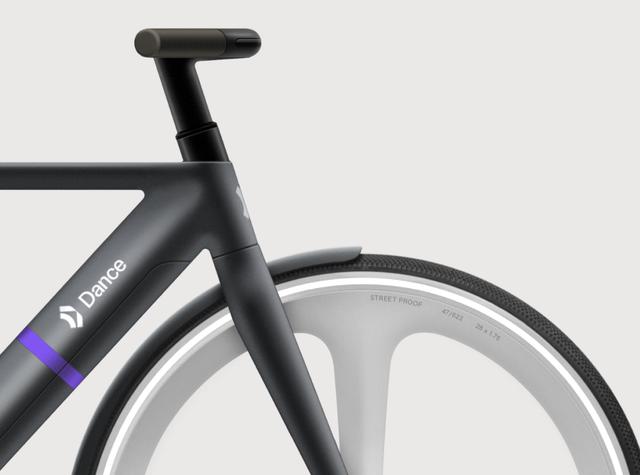 a close up of a black bike's handlebars and wheel