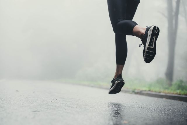 unrecognizable athlete jogging on the road during rainy day