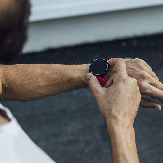 unrecognizable fit caucasian man running on the street taking the pulse from a smartwatch
