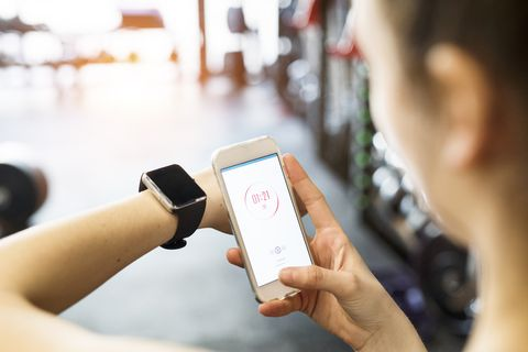 Unrecognizable fit woman in gym with smart phone and smart watch.