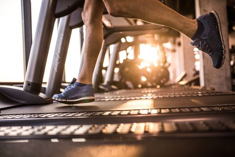 unrecognizable male athlete running on treadmill in health club
