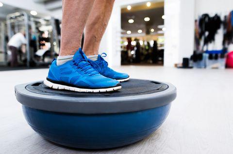 unrecognizable senior man in gym standing on bosu balance ball