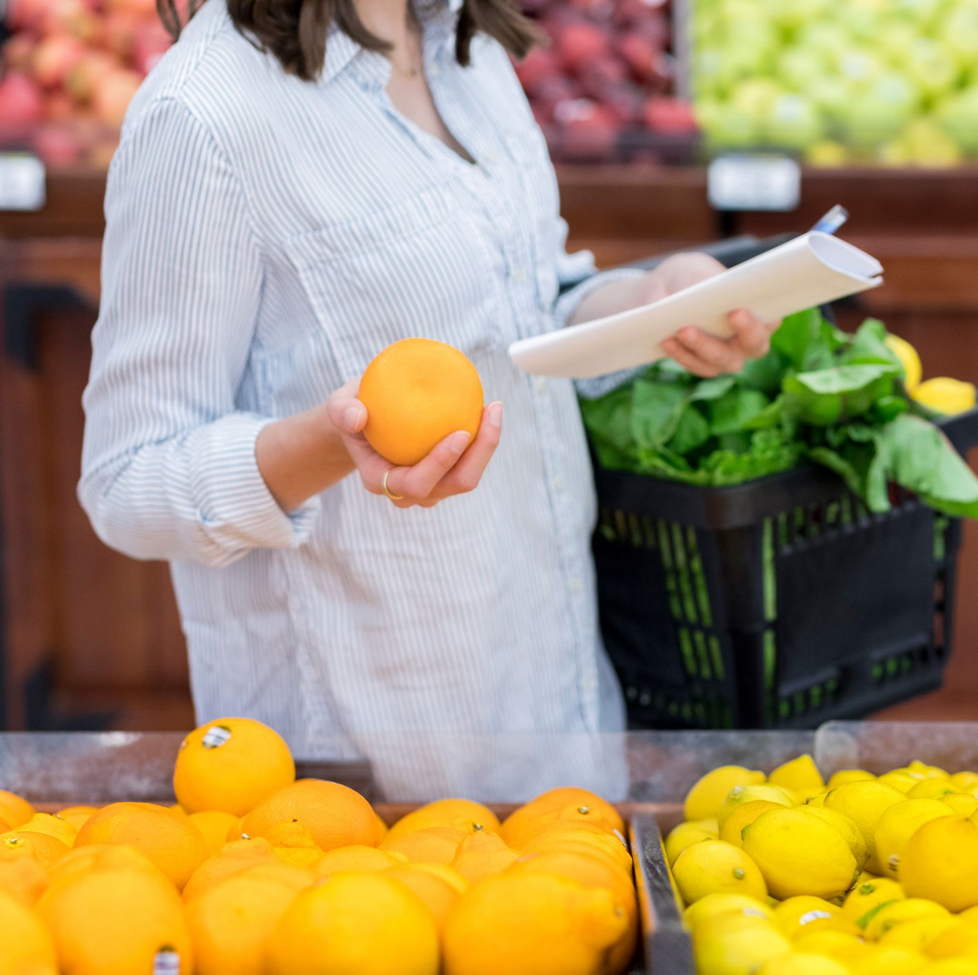 Unrecognizable woman shops for oranges