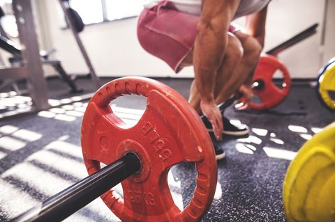 Unrecognizable young fit man in gym working out with heavy barbell, doing dead lift