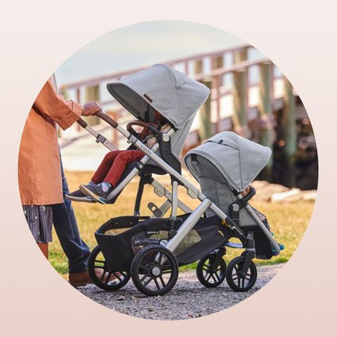 parents pushing uppababy single to double stroller