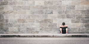 urban exhausted fitness man outdoor sitting on the floor