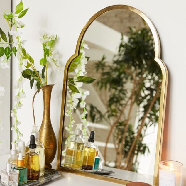 hanging macrame planter and arched mirror with gold frame