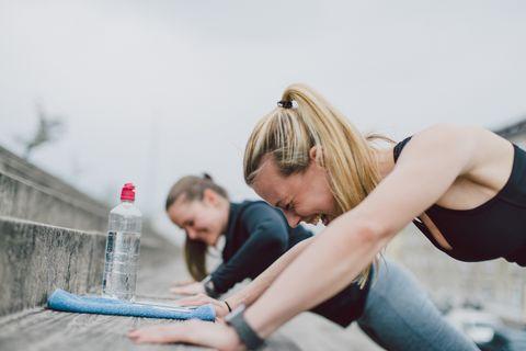Twee vrouwen zijnaan hetschaterlacht terwijl ze sporten.