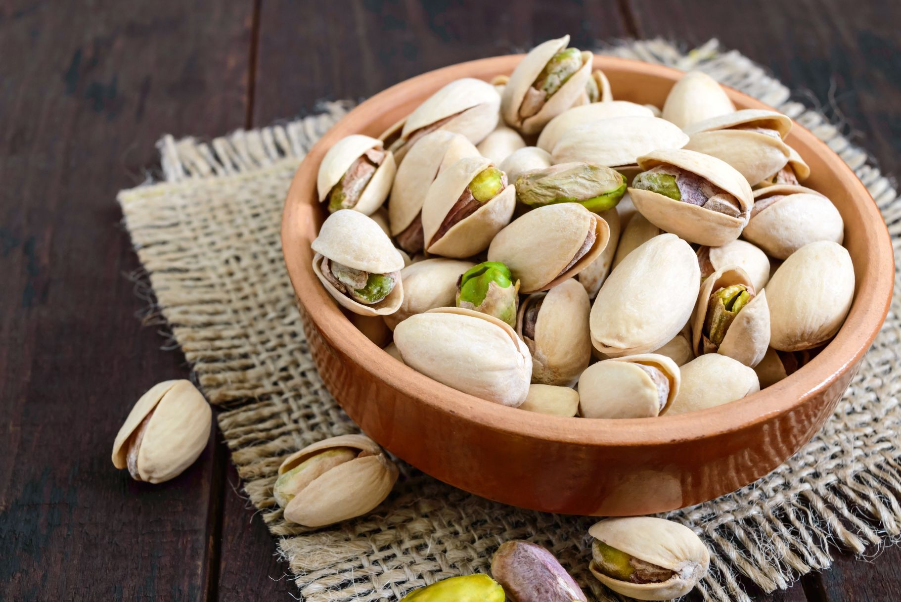 Useful nuts - pistachios in a ceramic bowl on a dark wooden background.