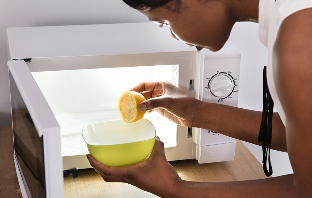 woman putting lemon in microwave