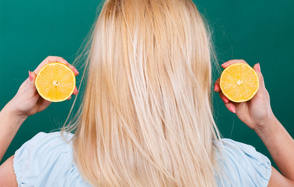 woman holding cut lemon near hair