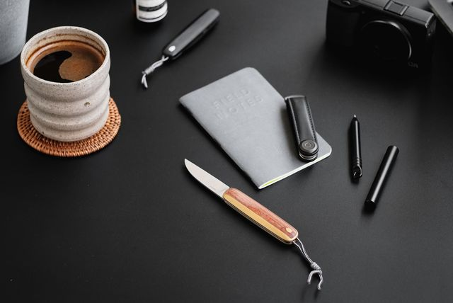 a pocket knife on a table with other items