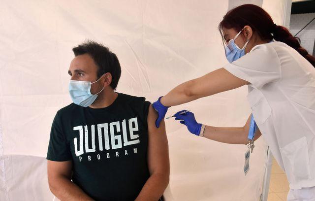 un hombre es vacunado con una dosis de pfizer contra la covid19