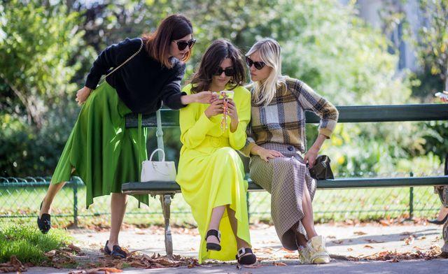 drie modemensen kijken op een telefoon