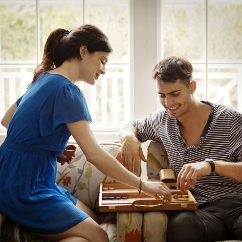 couple playing backgammon while sitting on armchair at home