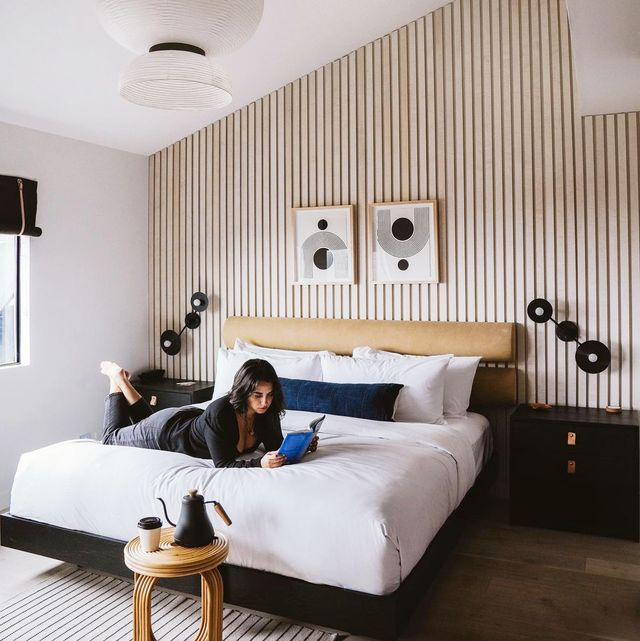 woman reading on bed in minimalist bedroom