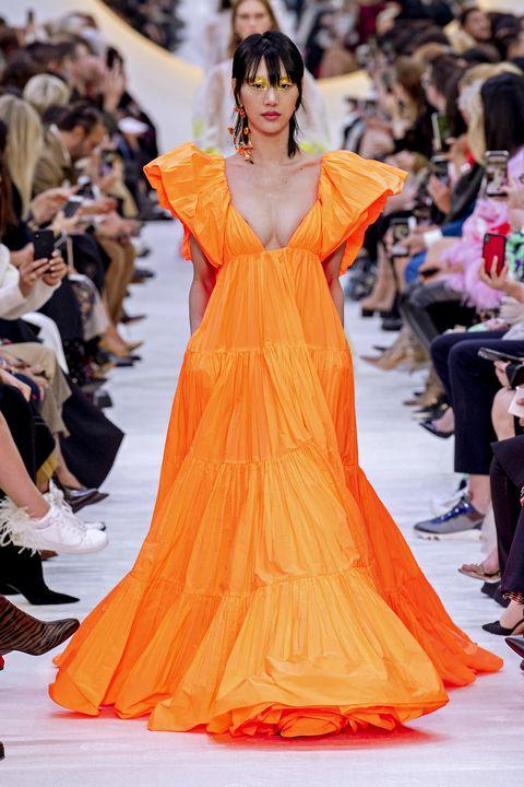 Fashion model, Fashion, Fashion show, Orange, Haute couture, Dress, Clothing, Yellow, Runway, Shoulder,