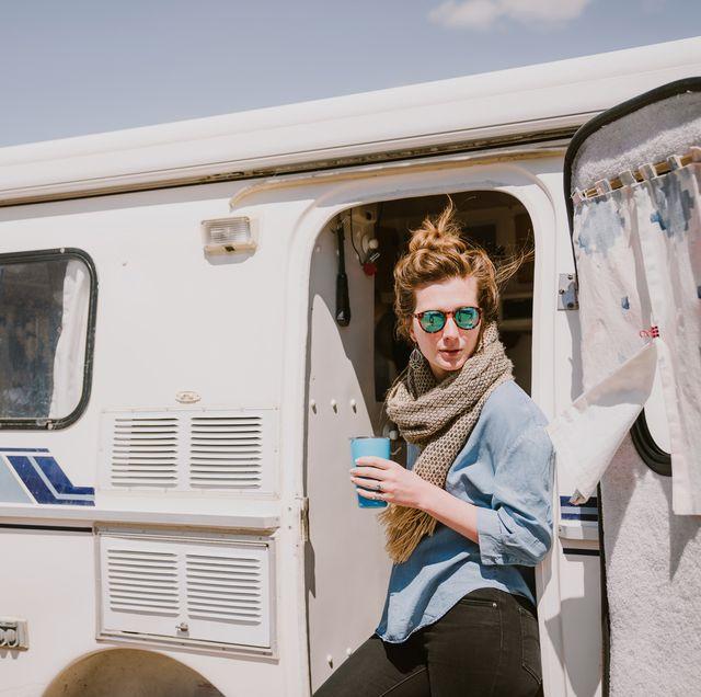 woman with coffee tumbler standing outside van in desert