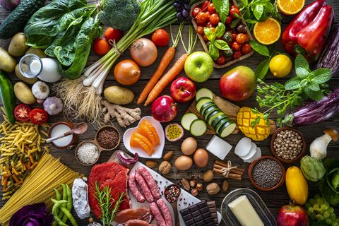 varied food carbohydrates protein vegetables fruits dairy legumes on wood