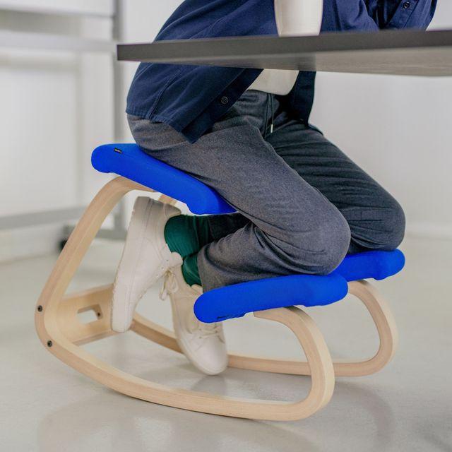 man sitting on blue varier kneeling chair