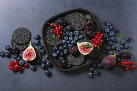 Variety of fresh berries blueberry, dewberry, red currant and figs with black charcoal crackers on wooden plate over dark metal background. Top view with space. Summer dark snacks concept