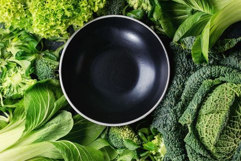 variety of raw green vegetables salads lettuce bok choy corn broccoli savoy cabbage round empty black ceramic bowl food background top view space for text