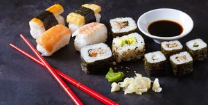 Variety of sushi with wasabi, ginger and bowl of soy sauce on dark ground