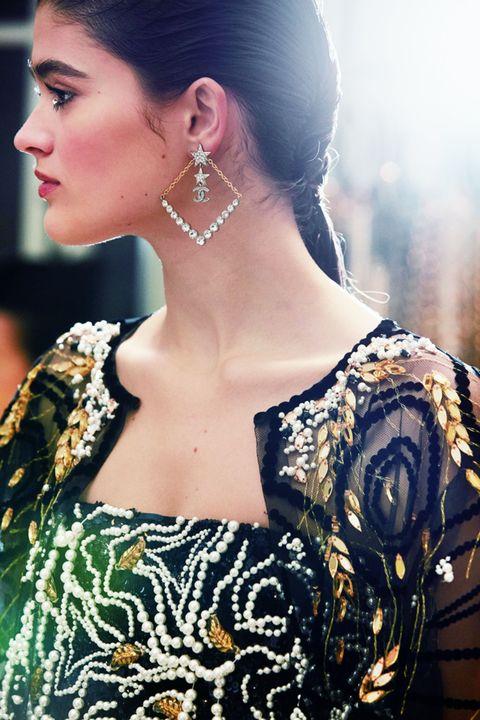 総ビーズの透け感のあるジャケットとドレスをまとったモデルの横顔