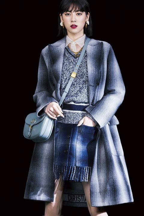 ネイビーのコートを着用したモデル写真