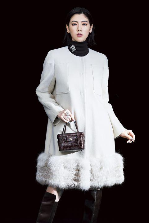 エクリュ色のコートを着たモデル写真