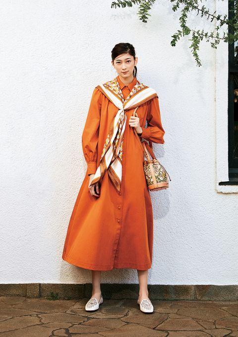 トリーバーチのオレンジのドレスを着用したモデル。